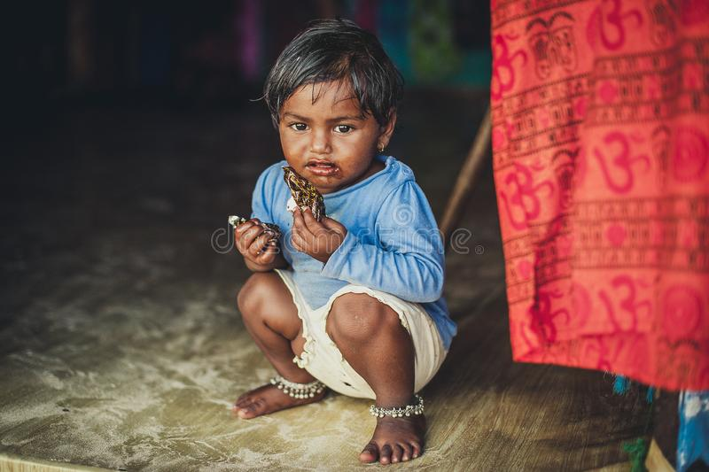 Poverty, a picture of a little poor Indian girl in old ragged clothes sitting on the floor. Chocolate baby stock photography