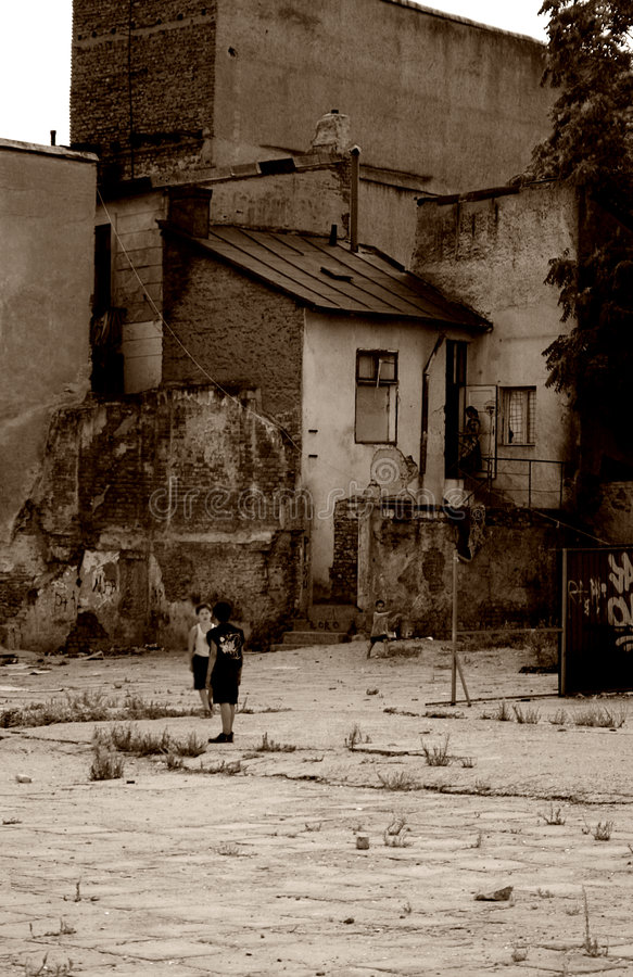 Poverty - poor children. Poverty - Old, degraded building, in a yard and poor children playing
