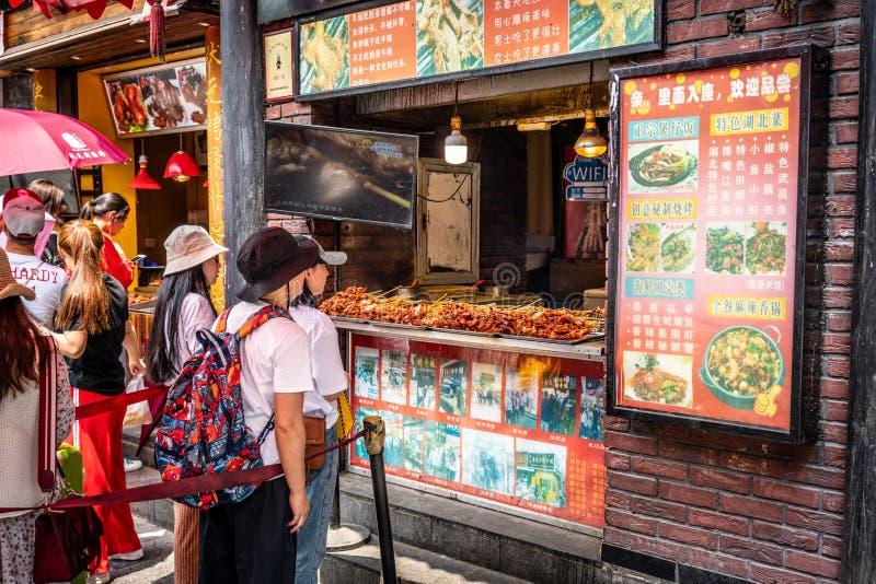 Povo chinês que enfileira-se para o alimento da rua dos espetos da carne na aleia de Hubu em Wuhan Hubei China imagem de stock