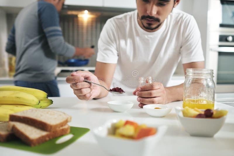 Povos alegres que comem o café da manhã que cozinha na cozinha home fotografia de stock royalty free