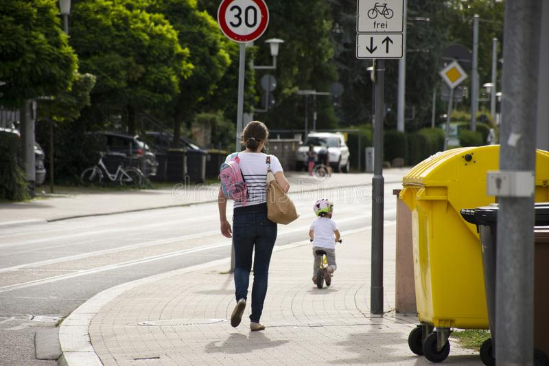 Povos alemães da mãe que olham a prática da menina das crianças que dá um ciclo no passeio ao lado da estrada em Heidelberg, Alem foto de stock royalty free
