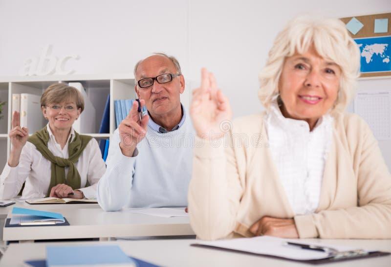 Povos aposentados que levantam as mãos fotos de stock