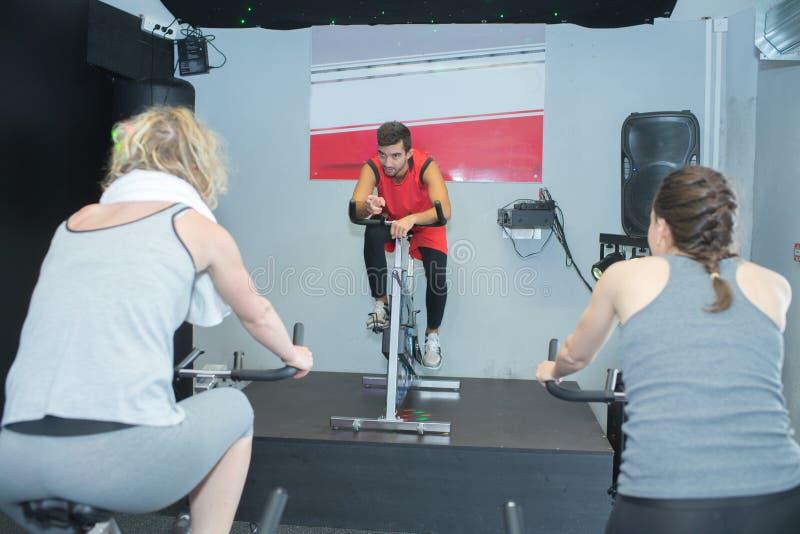 Povos aptos na classe da rotação no gym foto de stock