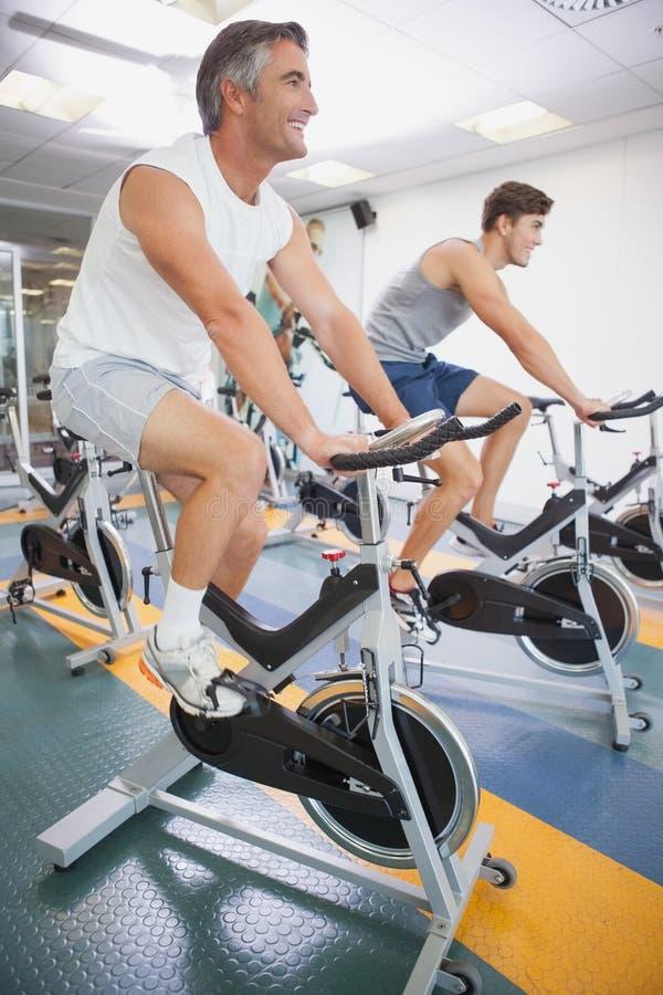 Povos aptos que dão certo nas bicicletas de exercício imagem de stock royalty free