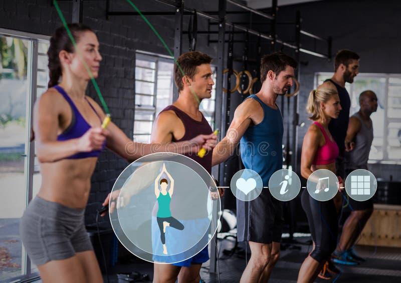 Povos aptos que executam cordas de salto no gym contra a relação da aptidão no fundo foto de stock