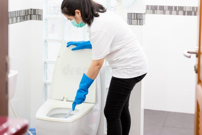 Povos asiáticos da mulher na luva azul com a bacia de toalete médica da limpeza da máscara usando a escova e no detergente, empre fotografia de stock royalty free
