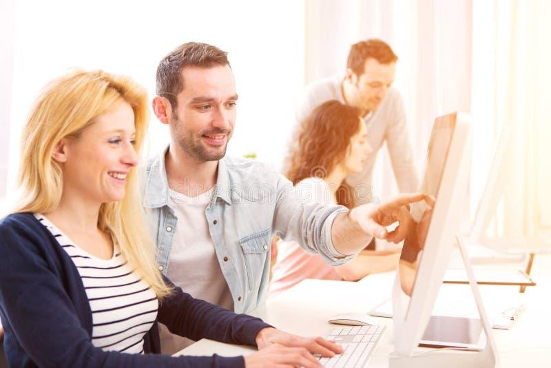 Povos atrativos novos que trabalham junto no escritório fotografia de stock royalty free