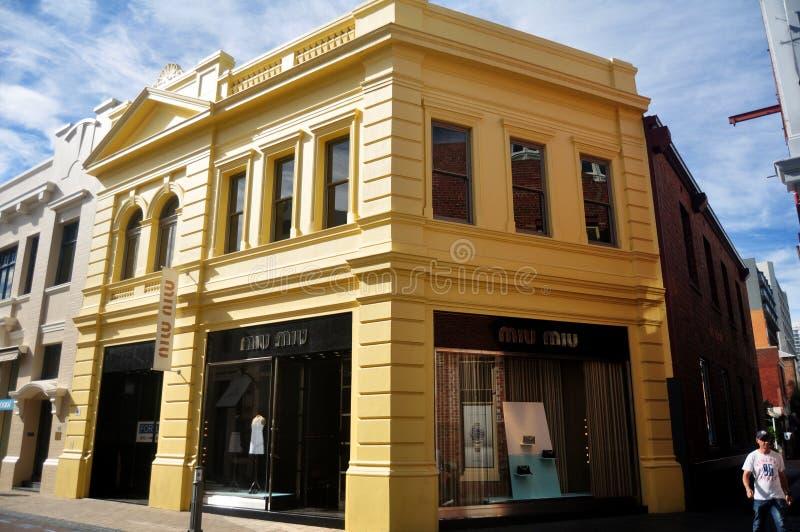 Povos australianos que andam no pavimento com construção clássica em Perth, Austrália imagem de stock