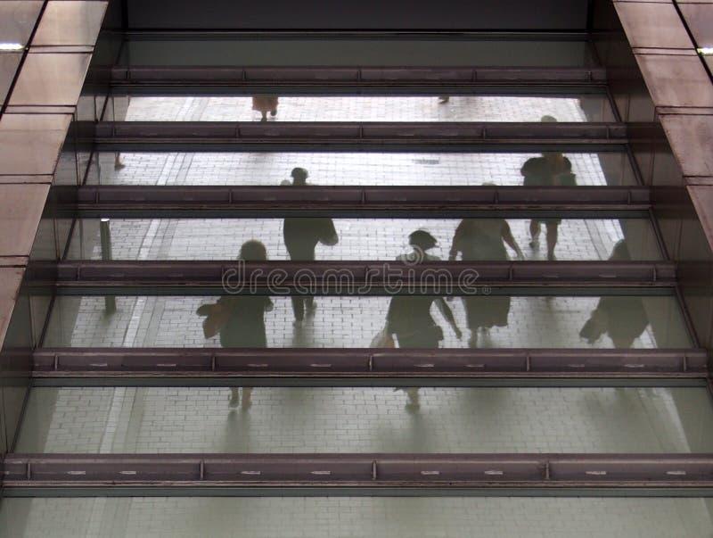 Povos borrados irreconhecíveis que andam com uma área pedestre refletida na janela de vidro de uma construção acima do sumário ur fotos de stock