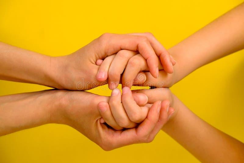 Povos, caridade, família e conceito do cuidado - próximo acima da mulher entrega guardar as mãos da menina fotos de stock royalty free