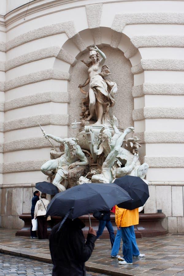 Povos com os guarda-chuvas na rua chuvosa imagens de stock