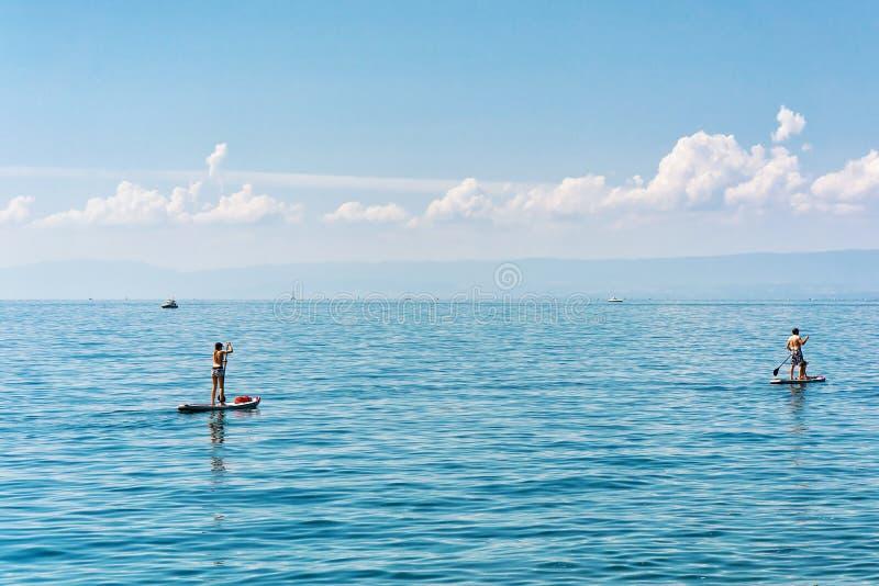 Povos com os suíços Standup Riviera do lago geneva da placa surfando da pá imagens de stock