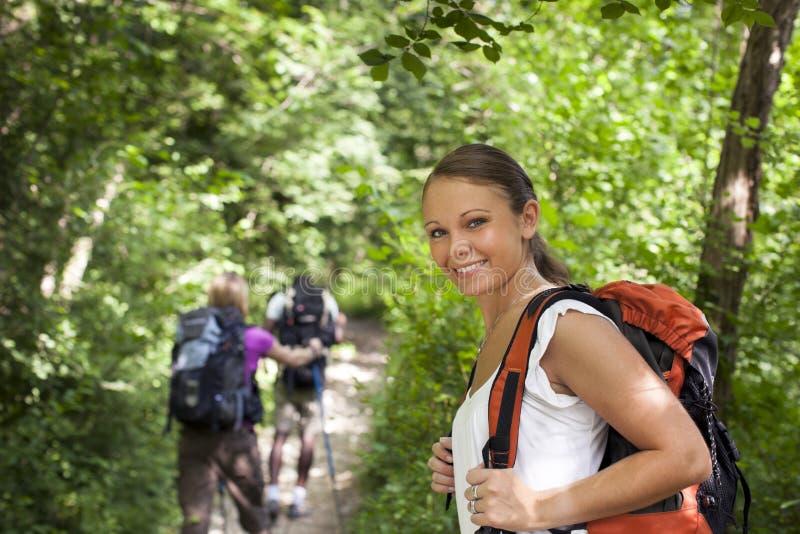 Povos com a trouxa que faz trekking na madeira imagem de stock royalty free