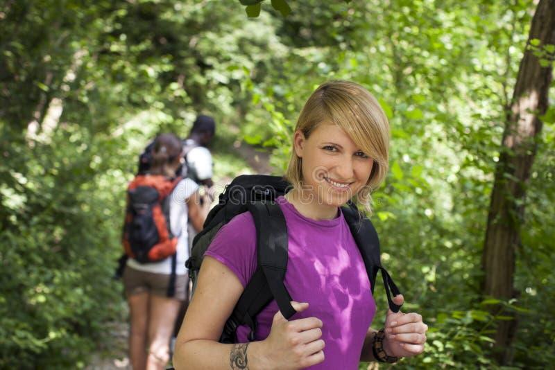 Povos com a trouxa que faz trekking na madeira fotos de stock