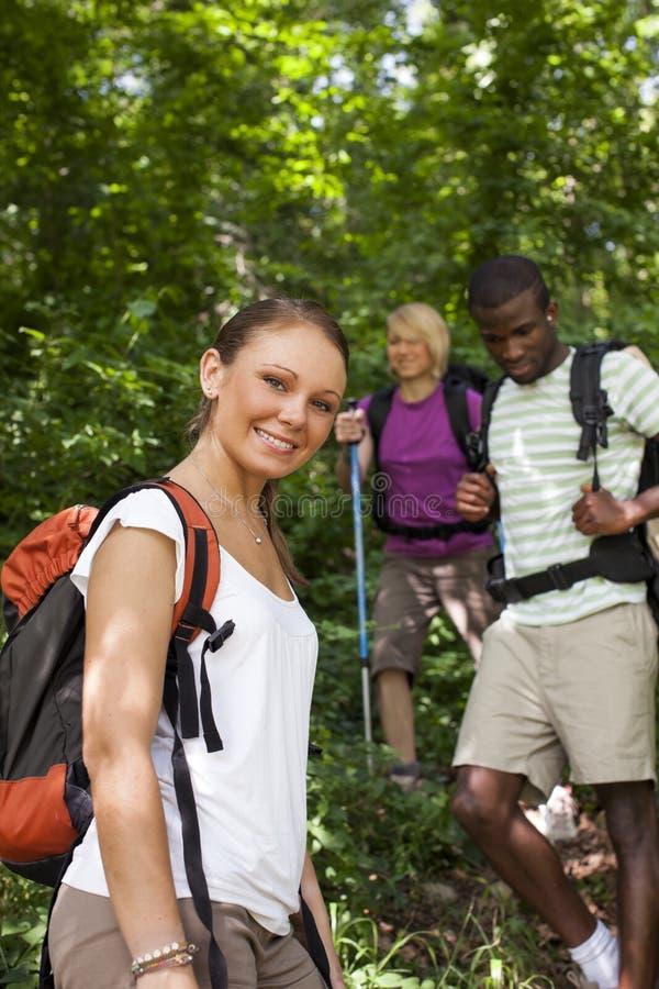 Povos com a trouxa que faz trekking na madeira fotos de stock royalty free
