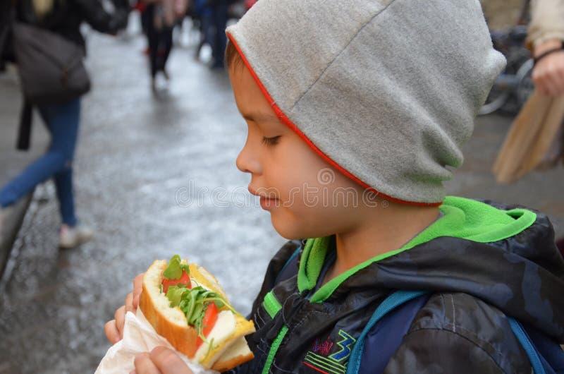 Povos, comida lixo, comer e estilo de vida - feche acima do homem novo, menino com sanduíche que come e que bebe na rua da cidade fotografia de stock royalty free