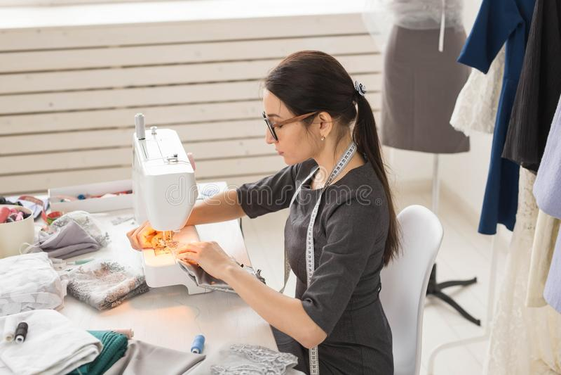 Povos, costureira e conceito da forma - retrato da vista lateral do desenhador de moda nos vidros usando a máquina de costura den fotos de stock