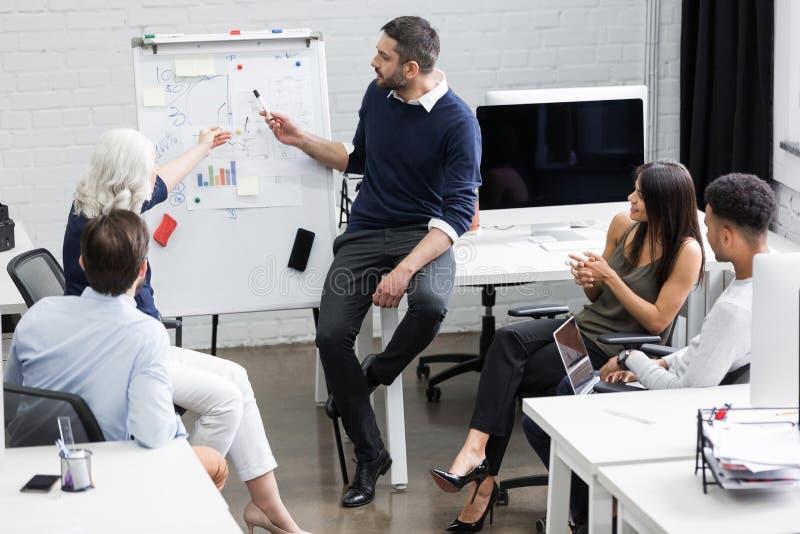 Povos criativos que sentam-se na tabela na sala de reuniões fotos de stock royalty free