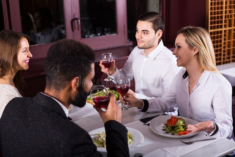 Povos da classe média que apreciam o alimento no café e na fala fotos de stock