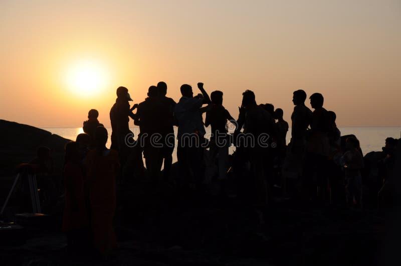 Povos da equipe da dança da silhueta. por do sol no mar fotos de stock royalty free
