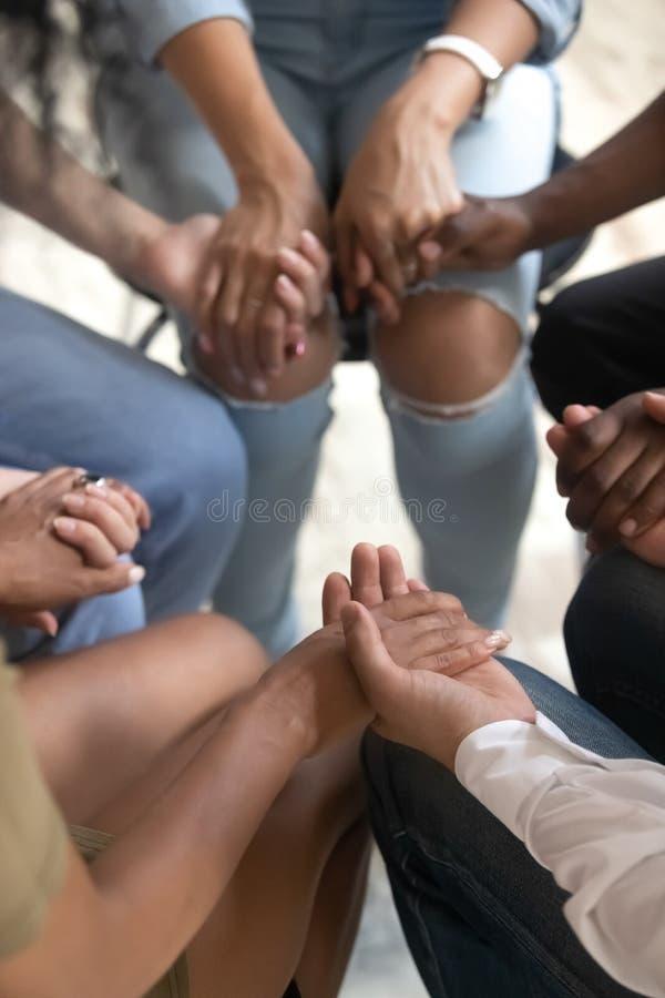 Povos da opinião do close up que sentam-se unidas mantendo as mãos durante a sessão de terapia fotografia de stock royalty free