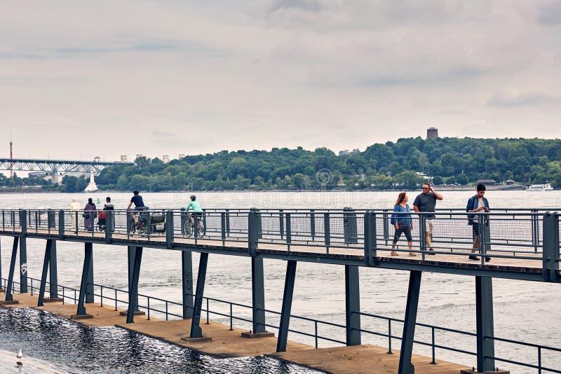 Povos da raça misturada que andam no passadiço pedestre sobre o Rio São Lourenço no porto velho de Montreal foto de stock royalty free