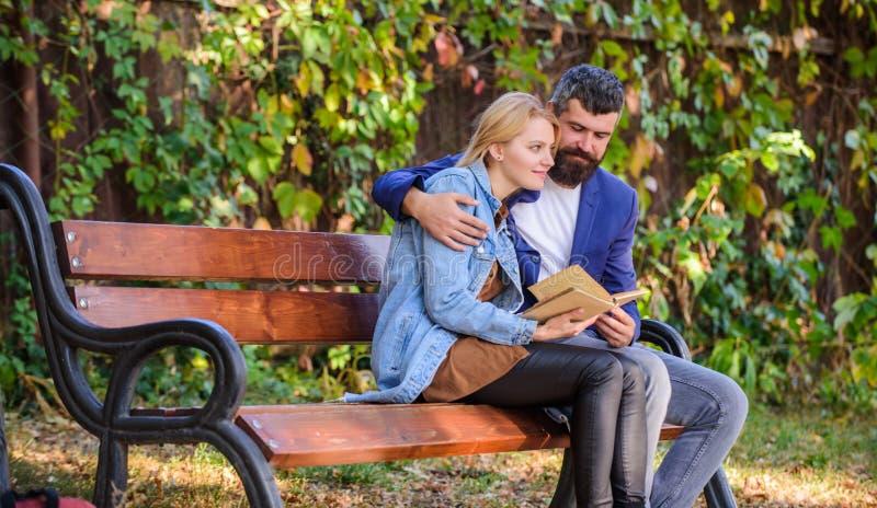Povos da reunião com interesses similares O homem e a mulher sentam o parque do banco Leia o mesmo livro junto Acople interessado imagens de stock