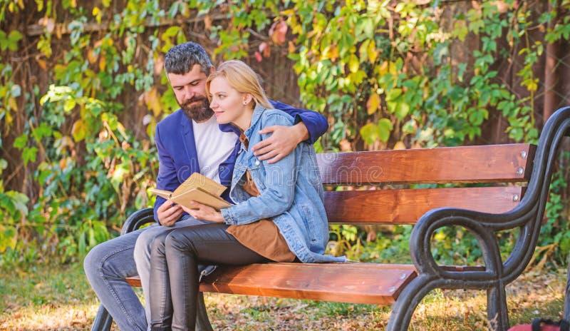 Povos da reuni?o com interesses similares O homem e a mulher sentam o parque do banco Leia o mesmo livro junto Acople interessado foto de stock
