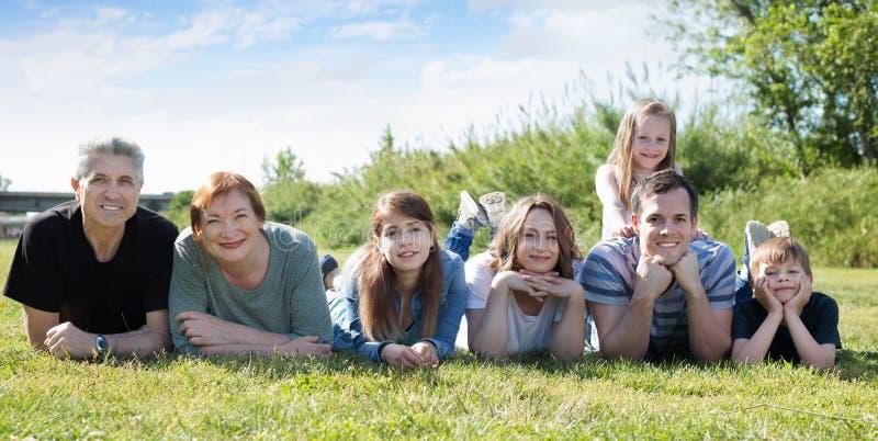 Povos das idades diferentes que tomam fotos no gramado fotografia de stock royalty free
