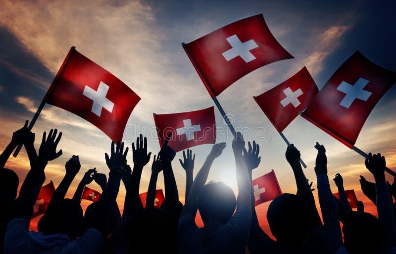 Povos das silhuetas que guardam o conceito de Suíça da bandeira foto de stock royalty free