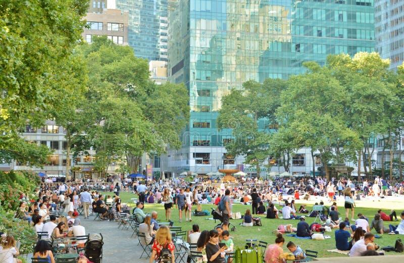 Povos de Bryant Park New York City que relaxam a atração turística aglomerada das horas de verão foto de stock royalty free