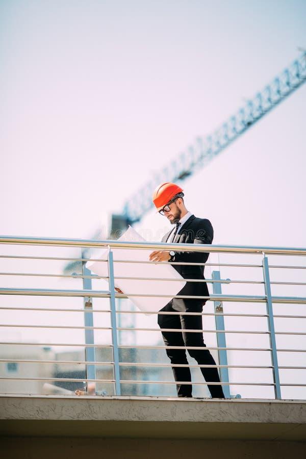 Povos de consulta da engenharia considerável do homem no canteiro de obras que guarda o modelo em sua mão Inspetor de construção  imagem de stock