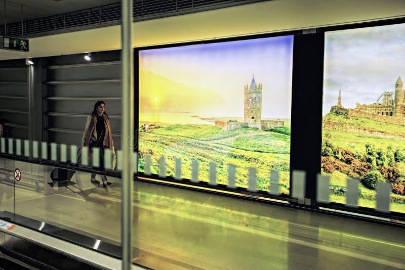 Povos de Dublin Airport, passageiros que viajam com as malas de viagem na escada rolante da passagem no movimento com imagens des fotos de stock royalty free