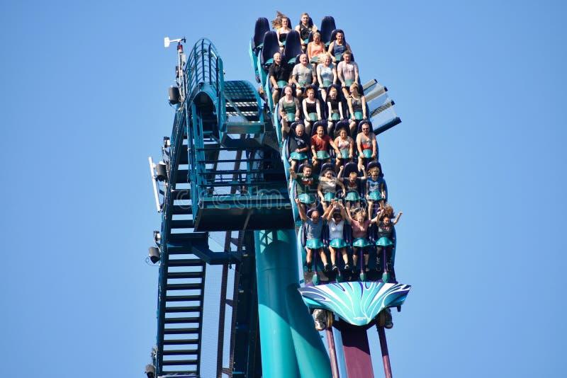 Povos de idades diferentes excitados e assustados pela descida rápida que monta Mako Roller Coaster em Seaw foto de stock