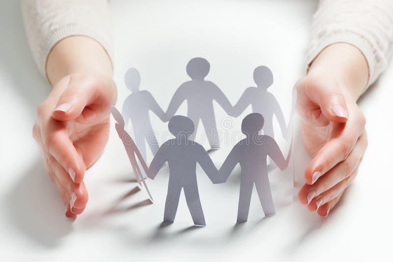 Povos de papel cercados pelas mãos no gesto da proteção Conceito do seguro foto de stock