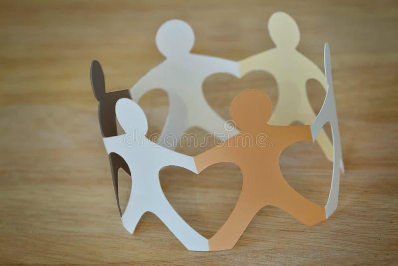 Povos de papel em um círculo que guarda as mãos - antirracismo e amor co imagem de stock royalty free