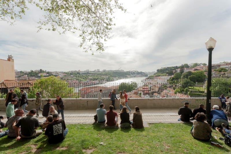 Povos de relaxamento no monte sobre o rio Douro, com amigos e arquitetura da cidade agradável da vista imagem de stock