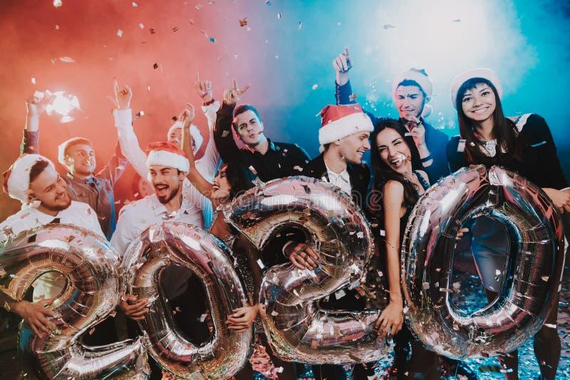 Povos de sorriso com Baloons que comemoram o ano novo imagem de stock