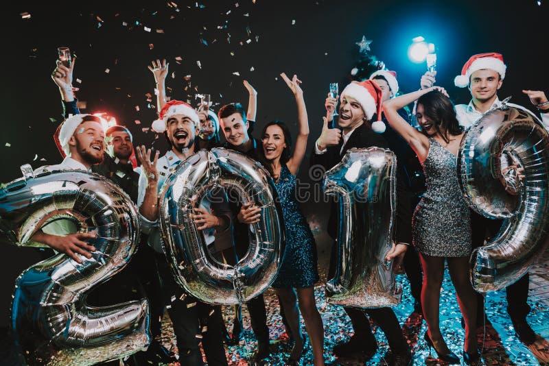 Povos de sorriso com Baloons que comemoram o ano novo imagens de stock