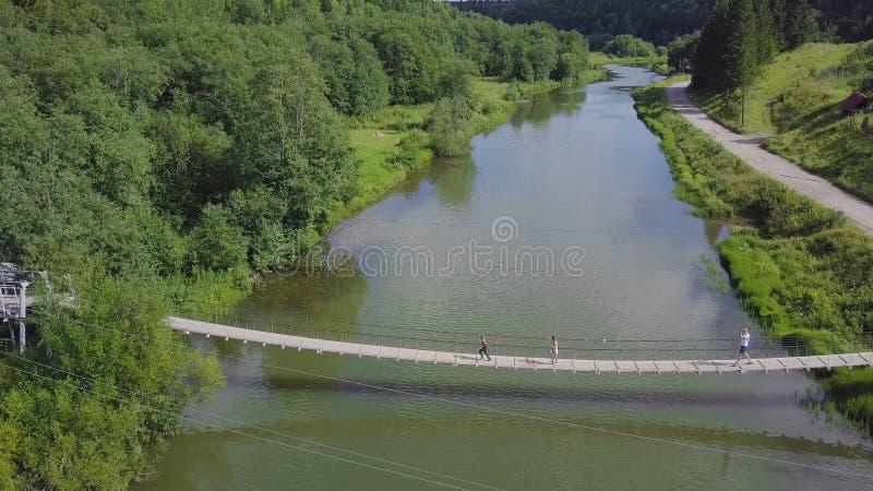 Povos de Unidenfied que andam sobre a ponte longa de suspensão do metal sobre o rio grampo Família na ponte sobre o rio imagens de stock royalty free