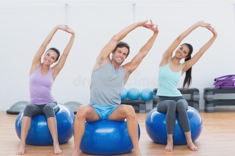 Povos desportivos que esticam acima das mãos em bolas do exercício no gym imagens de stock royalty free