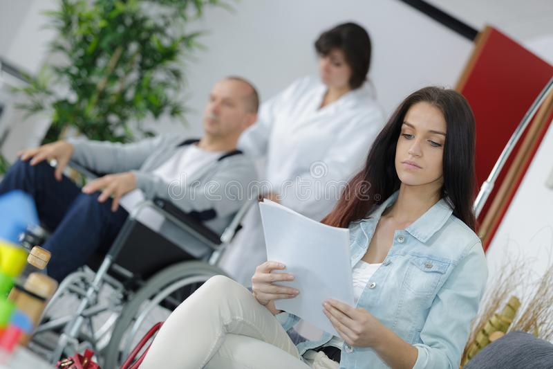 Povos diferentes que sentam-se no hospital da sala de espera imagem de stock
