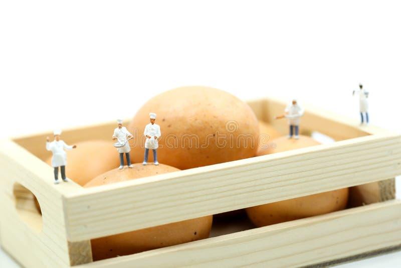 Povos diminutos: Cozinheiro chefe durante o cozimento e o trabalho com ovos imagens de stock royalty free