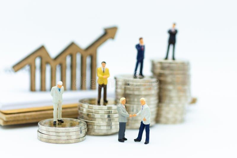 Povos diminutos: Equipe do homem de negócios que está na pilha de moeda Uso para financeiro, conceito da imagem da visão do negóc fotos de stock royalty free