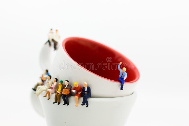 Povos diminutos: Equipe do negócio que senta-se na xícara de café e que tem uma ruptura de café Uso da imagem para o conceito do  foto de stock