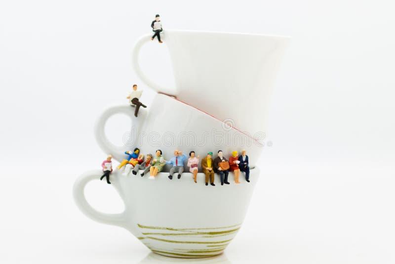 Povos diminutos: Equipe do negócio que senta-se na xícara de café e que tem uma ruptura de café Uso da imagem para o conceito do  imagem de stock royalty free