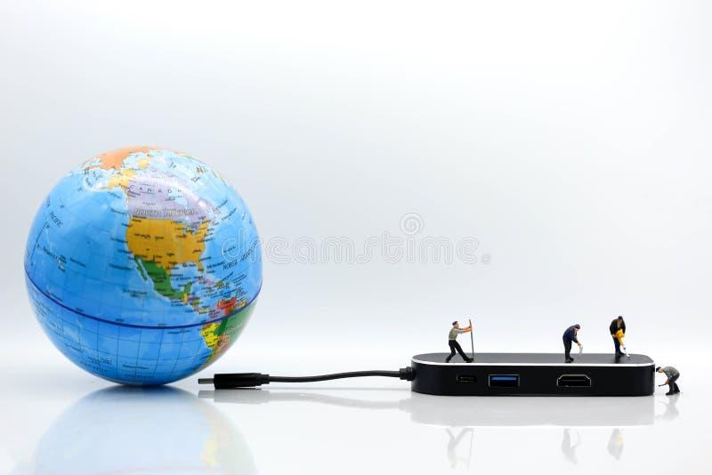 Povos diminutos: equipe do trabalhador com cabo do usb do mundo miliampère do globo imagem de stock royalty free