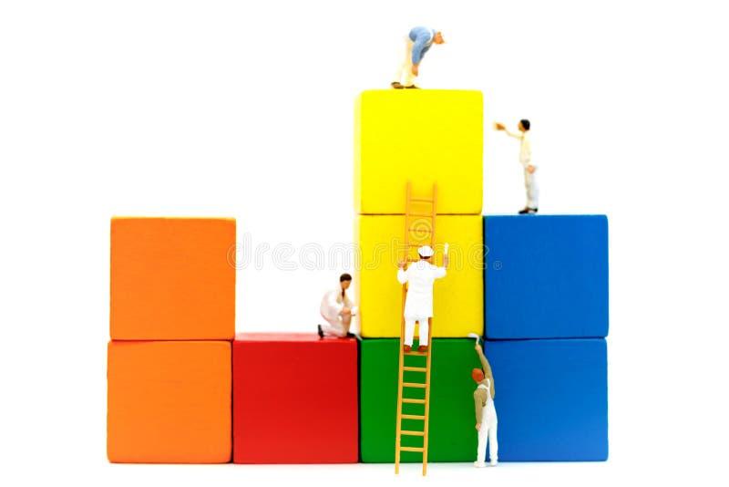 Povos diminutos: Escova da equipe dos trabalhadores que pinta a barra financeira imagem de stock