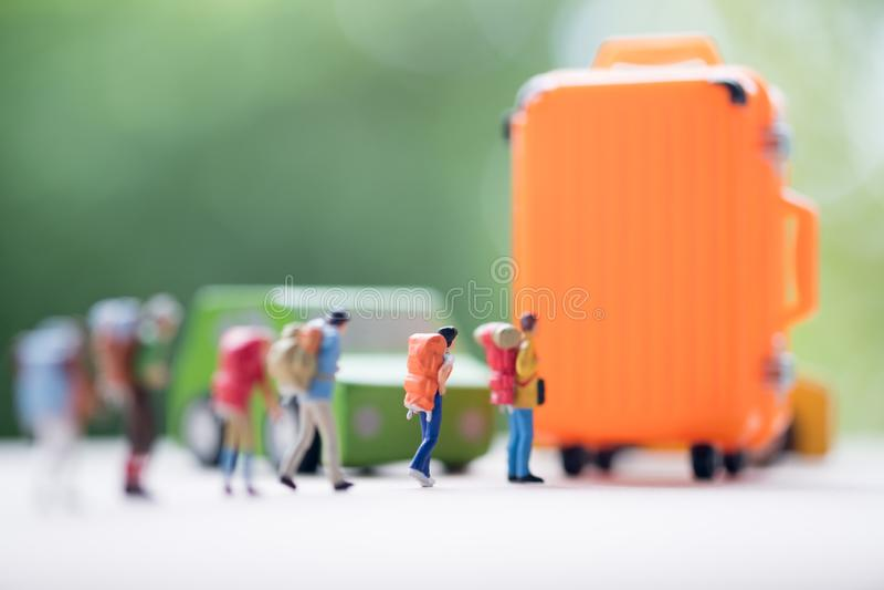 Povos diminutos: Grupo de viajantes com mala de viagem alaranjada fotos de stock