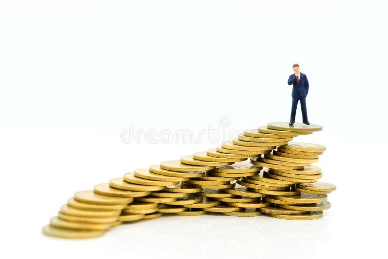 Povos diminutos: Homem de negócios que levanta-se em um aumento empilhado moeda respectivamente, usado como um conceito do negóci fotografia de stock
